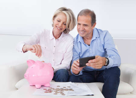 Foto de Happy Mature Couple Calculating Coin In The Piggybank - Imagen libre de derechos