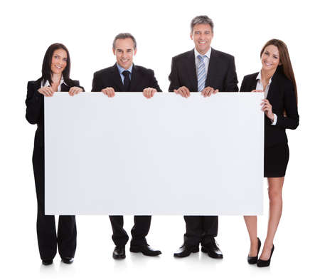 Foto de Portrait Of Business People Holding Placard Over White Background - Imagen libre de derechos