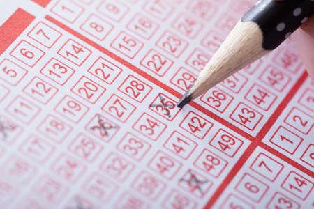 Foto de Close-up Of A Person Marking Number On Lottery Ticket With Pencil - Imagen libre de derechos