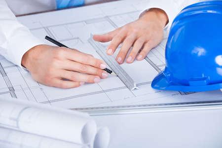 Foto de Close-up Of Male Architect Working On Blueprint At Desk - Imagen libre de derechos