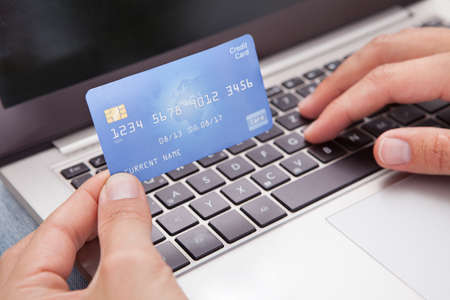 Photo pour Young Man Sitting With Laptop And Credit Card Shopping Online - image libre de droit