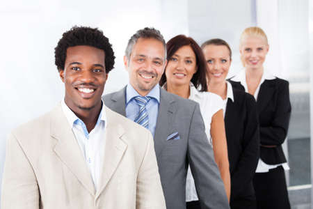 Foto de Group Of Happy Multiracial Businesspeople Standing In A Row - Imagen libre de derechos