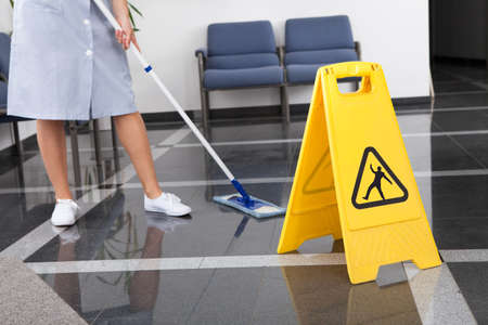 Photo pour Maid Cleaning The Floor With Mop In Office - image libre de droit