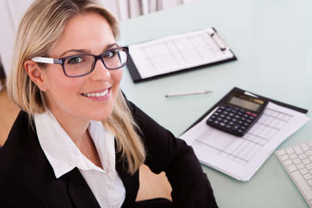 Photo pour Young Businesswoman Calculating Data In Her Office - image libre de droit