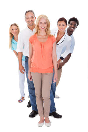 Foto de Group Of Multi-racial People Standing In A Row On White Background - Imagen libre de derechos