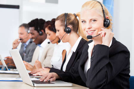 Photo pour Happy Co-workers Wearing Headsets Working In Call Center - image libre de droit