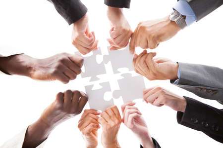 Photo pour Close-up Photo Of Businesspeople Holding Jigsaw Puzzle - image libre de droit