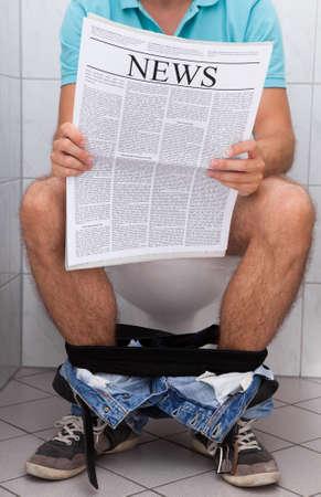 Photo pour Close-up of a man in toilet reading newspaper indoors - image libre de droit