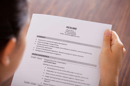 Photo for Close-up Of Young Businesswoman Reading Resume At Desk - Royalty Free Image