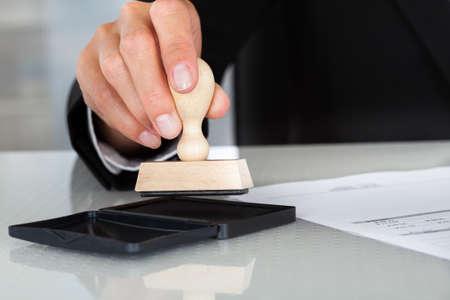 Photo pour Close-up Of Business Man Hand Pressing Rubber Stamp On Document - image libre de droit