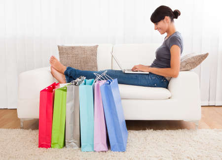 Photo for Young Beautiful Woman Sitting On Couch Shopping Online - Royalty Free Image