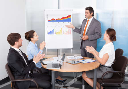 Group Of Colleagues Appreciating Businessman At Presentation