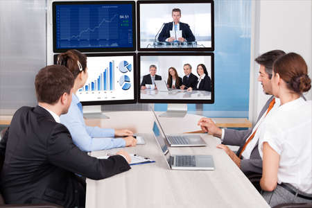 Photo for Businesspeople Sitting In A Conference Room Looking At Computer Screen - Royalty Free Image