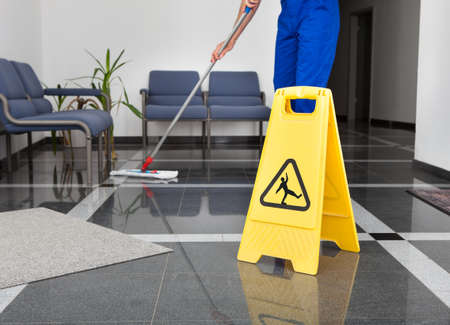 Photo pour Close-up Of Man Cleaning The Floor With Yellow Wet Floor Sign - image libre de droit