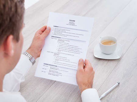 Photo for Close-up Of Businessman Reading Resume With Tea Cup On Desk - Royalty Free Image