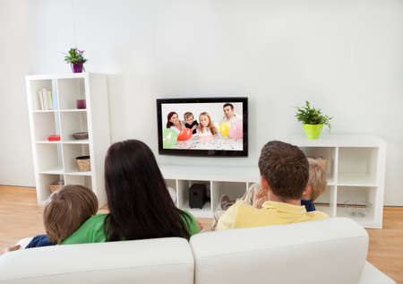 Foto de Young happy family watching TV at home - Imagen libre de derechos