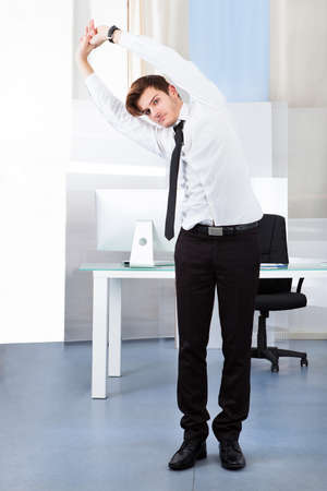 Portrait Of A Young Businessman Stretching In Office