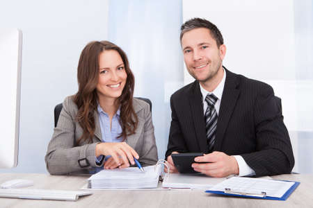 Photo pour Two Young Businesspeople Calculating Bills At Desk In Office - image libre de droit