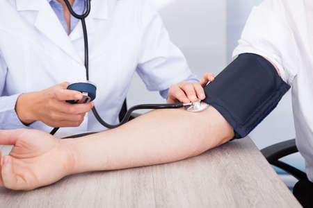 Foto de Close-up Of Female Doctor's Hand Checking Blood Pressure - Imagen libre de derechos