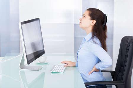 Photo pour Portrait Of Young Businesswoman Suffering From Back Pain - image libre de droit