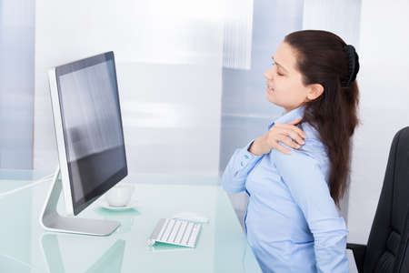 Photo pour Young Businesswoman Using Computer Suffering From Neck Ache - image libre de droit