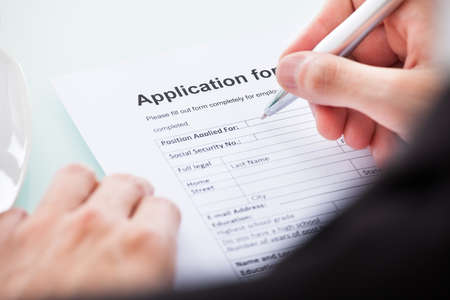 Photo pour Close-up Of Man's Hand Filling Application For Employment - image libre de droit