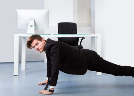 Young Businessman Doing Pushups At His Workplace