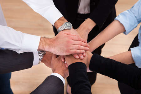 Photo pour Close-up Of Businesspeople Putting Their Hands On Top Of Each Other - image libre de droit
