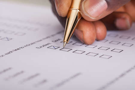 Photo pour Close-up Of Businessman Filling Customer Survey Form - image libre de droit