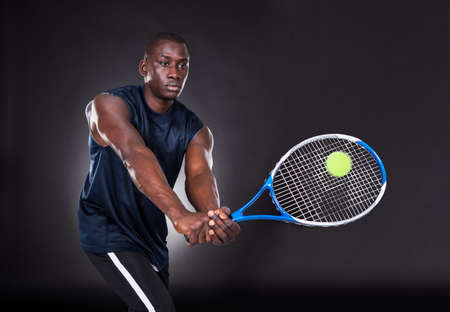 Portrait Of Young African Man Playing Tennis On Black