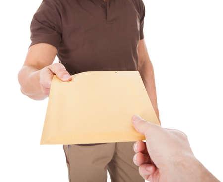 Foto de Close-up Of Mailman Delivering Mail To Person Over White  - Imagen libre de derechos