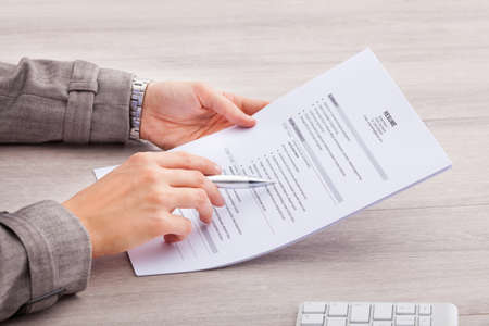 Photo for Close-up Of A Businesswoman At Desk Holding Resume - Royalty Free Image
