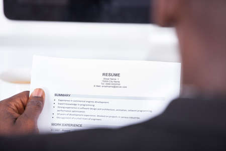 Photo for Close-up Of A Businessman Looking At Resume Holding In Hand - Royalty Free Image