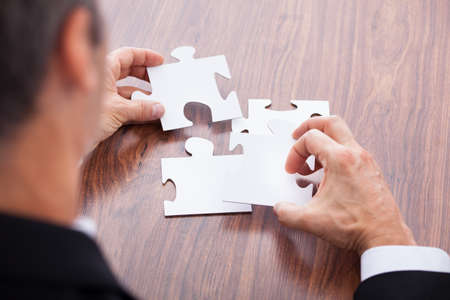 Portrait Of A Mature Businessman Solving Jigsaw Puzzle In Office
