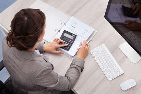 Photo pour High Angle View Of Young Female Accountant Calculating Bills - image libre de droit