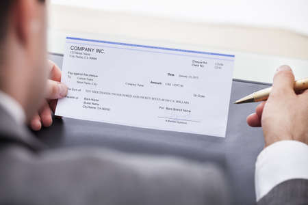 Photo pour Close-up Of A Businessman Filling Blank Cheque - image libre de droit
