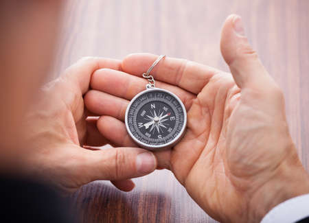 Close-up Of Hand Holding Compass On White Background