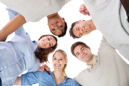 Photo pour Happy Group Of People In Circle Looking Down Over White Background - image libre de droit