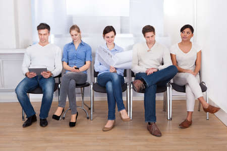 Photo for Group Of People Sitting On Chair In A Waiting Room - Royalty Free Image