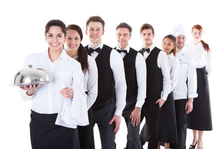 Foto de Large group of waiters and waitresses standing in row. Isolated on white - Imagen libre de derechos