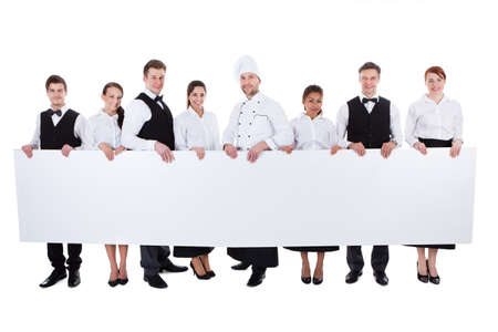 Foto de Large group of catering staff holding a blank banner with copyspace for your text including a chef  waiters  waitresses  hostess and wine steward  isolated on white - Imagen libre de derechos