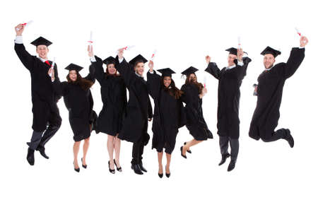 Photo pour Happy rejoicing group of multiethnic graduates leaping in the air cheering as they celebrate the successful completion of their academic studies  isolated on white - image libre de droit