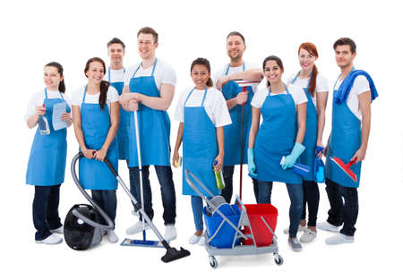 Photo pour Large diverse group of janitors wearing blue aprons standing grouped together with their equipment smiling at the camera  isolated on white - image libre de droit