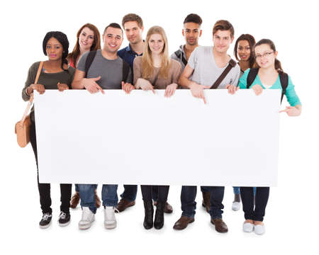 Photo for Full length portrait of confident multiethnic college students displaying blank billboard against white background - Royalty Free Image