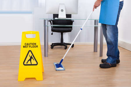Photo pour Yellow warning notice to caution people to a slippery wet surface as a janitor mops the floor in an office building - image libre de droit
