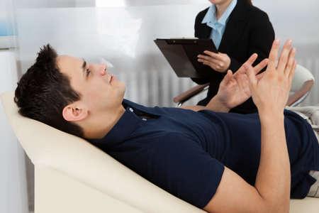 Foto de Female psychologist writing notes while patient lying on bed in clinic - Imagen libre de derechos