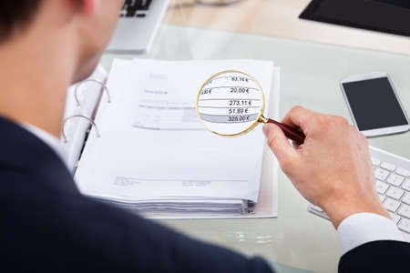 Photo for Cropped image of auditor examining invoice with magnifying glass at desk - Royalty Free Image