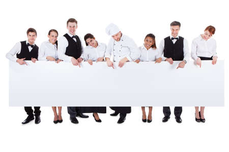 Photo for Large group of catering staff holding a blank banner with copyspace for your text including a chef  waiters  waitresses  hostess and wine steward  isolated on white - Royalty Free Image