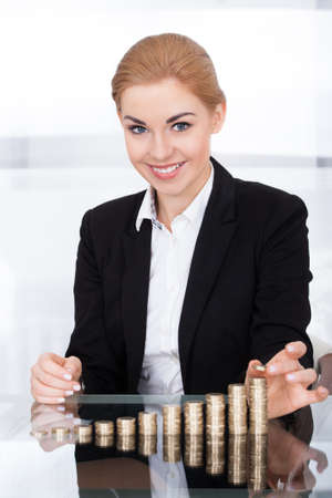 Portrait Of A Young Businesswoman Stacking Coins On Desk