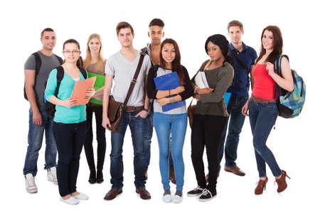 Foto de Full length portrait of confident college students standing together against white background - Imagen libre de derechos